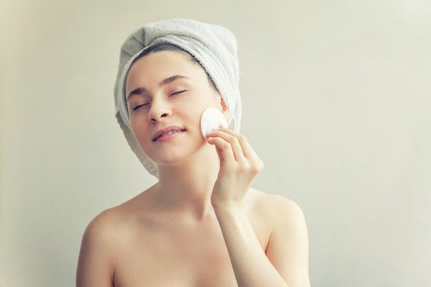 Smiling woman in towel on head with soft healthy skin removing make up with cotton pad isolated
