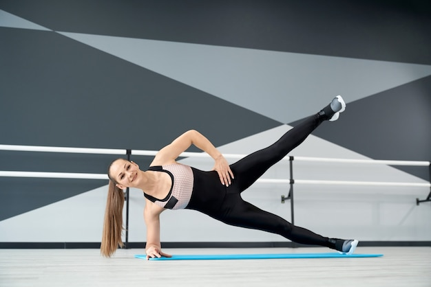 Smiling woman training on mat in hall