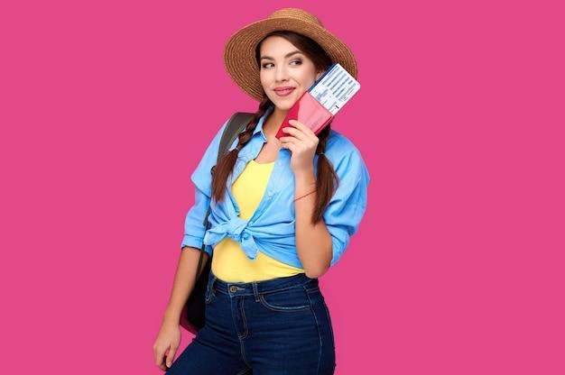 Улыбающаяся женщина-путешественница в соломенной шляпе и рюкзаке держит паспорт с билетом на самолет на розовом фоне изолировать