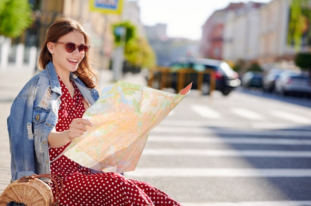 Smiling woman traveler sitting on the ground in the city and uses paper map