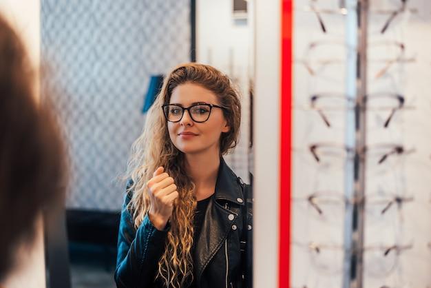 鏡を見て新しいメガネをしようとしている女性の笑みを浮かべてください。