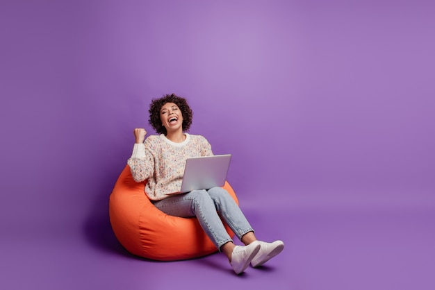 Smiling woman typing on laptop computer rejoice victory raise fist shout sit beanbag on purple wall