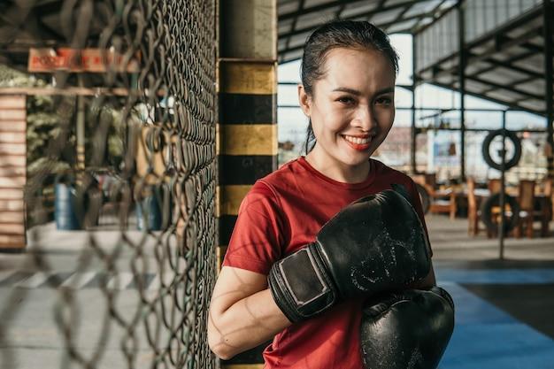 팔각형 반지 근처에 서 권투 장갑에 웃는 여자 궁극 전투기