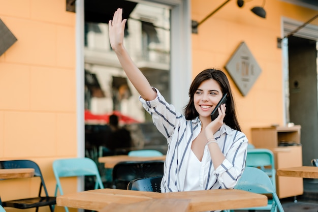 Smiling woman uses phone sitting in cafe