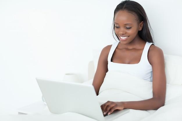 睡眠の前にラップトップを使用して笑顔の女性
