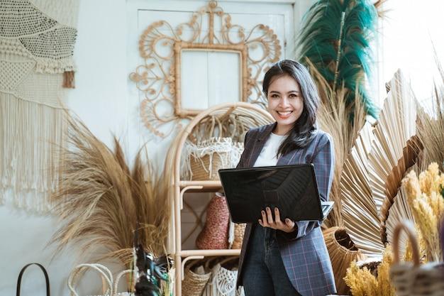 Улыбающаяся женщина с ноутбуком, стоя у стены в ремесленном магазине