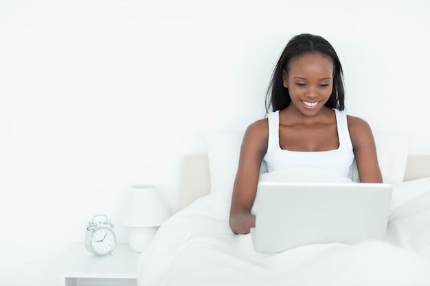 眠る前にノートパソコンを使って笑顔の女性
