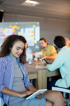 Улыбающаяся женщина с помощью цифрового планшета в офисе