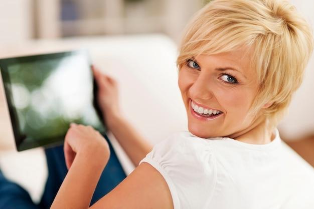 Donna sorridente utilizzando la tavoletta digitale a casa