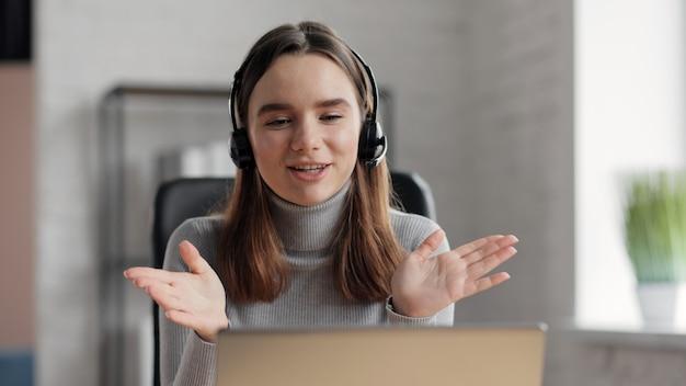Улыбающаяся женщина с помощью ноутбука и беспроводной гарнитуры для онлайн-встреч, видеозвонков, видеоконференций.