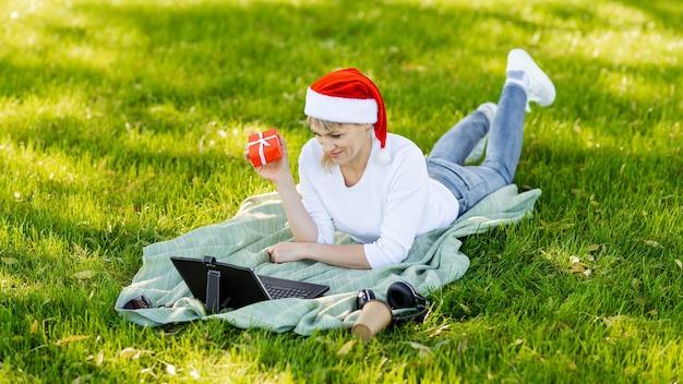 Улыбающаяся женщина с помощью ноутбука в парке. фрилансер печатает на ноутбуке
