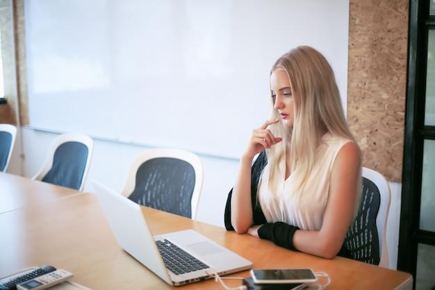 청중을 끌어 들이고 콘텐츠 제작을 확장하려는 소규모 비즈니스를 위해 직장에서 랩톱을 사용하는 웃는 여성은 작업 공간에서 새로운 마케팅 기술을 채택 할 수 있습니다. 프리랜서 개념.