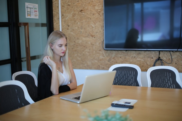 Улыбающаяся женщина, использующая ноутбук на рабочем месте для малого бизнеса, стремящегося привлечь аудиторию и масштабное создание контента, может внедрить новую маркетинговую технологию в рабочее пространство. концепция фрилансера.