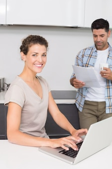 Smiling woman using laptop while partner reads the newspaper