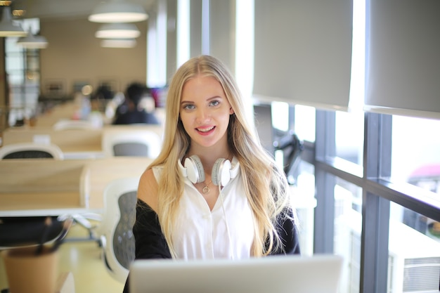 Smiling woman using laptop in work place for small businesses looking to engage audiences and scale content creation can adopt new marketing technology in workspace. freelancer concept.