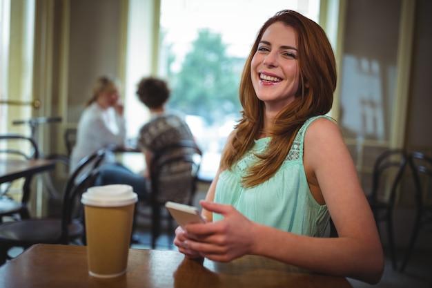 Donna sorridente con il cellulare in caffetteria ©