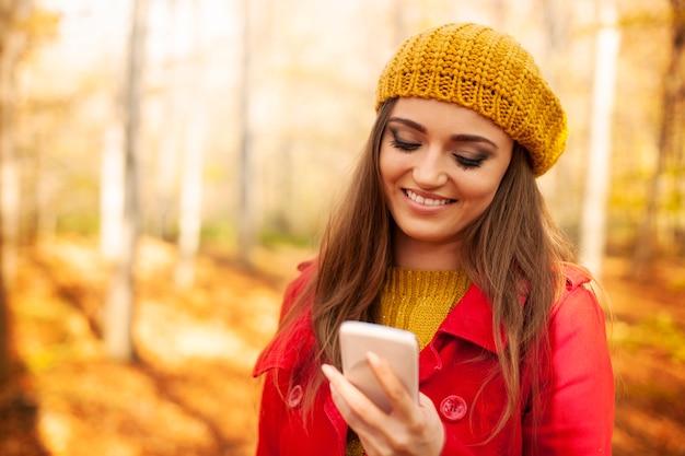 秋の間に公園で携帯電話を使用して笑顔の女性
