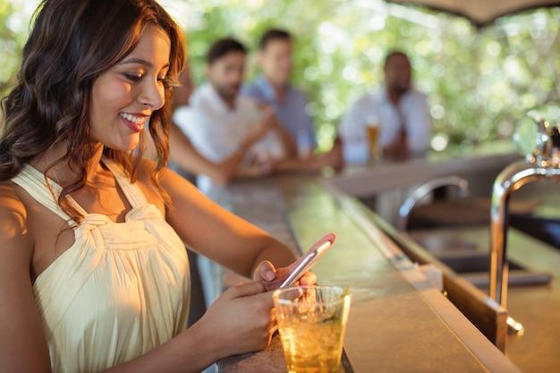 Улыбающаяся женщина с помощью мобильного телефона за бокалом пива