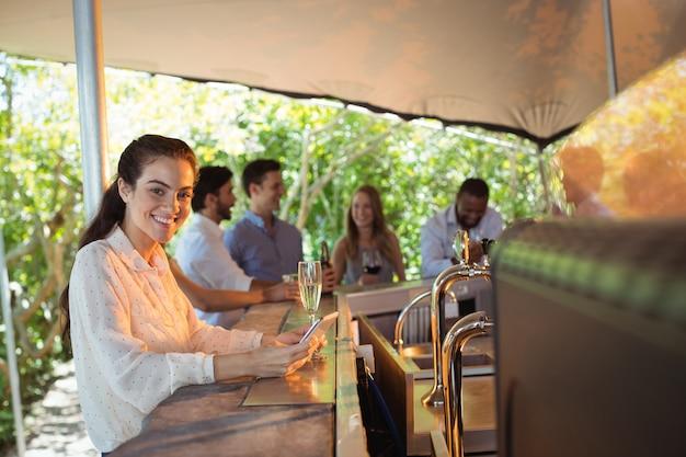 Улыбающаяся женщина с помощью мобильного телефона за бокалом шампанского в ресторане