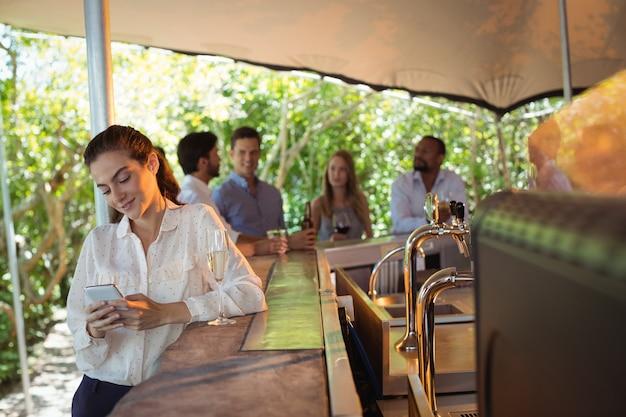 Улыбающаяся женщина с бокалом шампанского с помощью мобильного телефона
