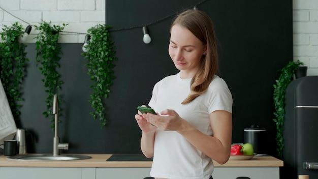 Улыбающаяся женщина с помощью смартфона на кухне