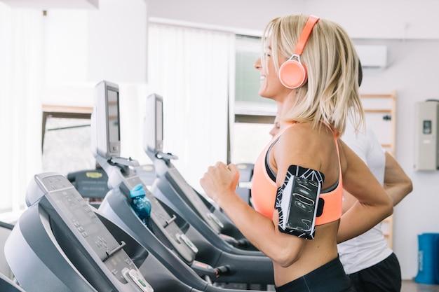Smiling woman using treadmill