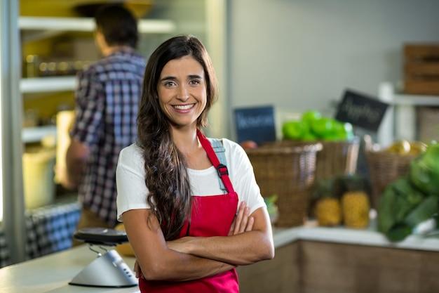 Улыбающаяся женщина-продавец, стоящая у прилавка в продуктовом магазине со скрещенными руками