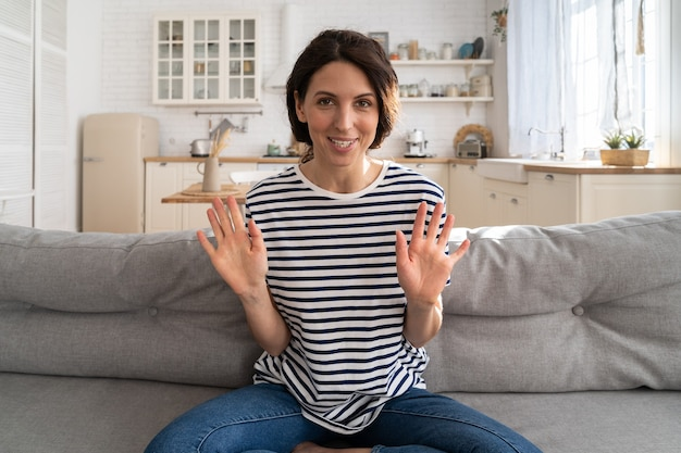 Улыбающаяся женщина-влиятельный блогер записывает новый контент в видеоблог, глядя на веб-камеру, сидя на диване.