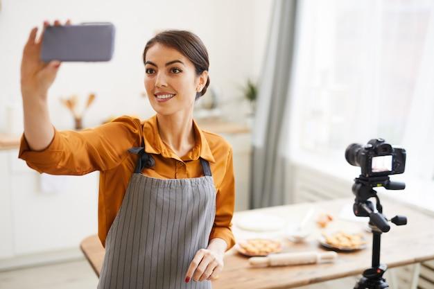 Smiling woman vlogging in kitchen