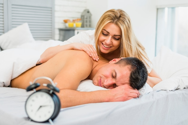 Smiling woman waking up man near snooze in bed