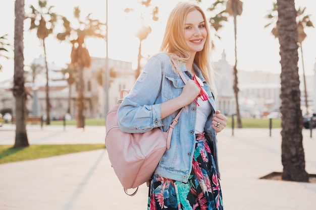 Smiling woman walking in city street in stylish denim oversize jacket, holding pink leather backpack