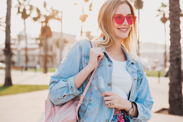 Smiling woman walking in city street in stylish denim oversize jacket wearing pink sunglasses, holding leather backpack