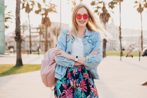 Smiling woman walking in city street in stylish printed skirt and denim oversize jacket wearing pink sunglasses