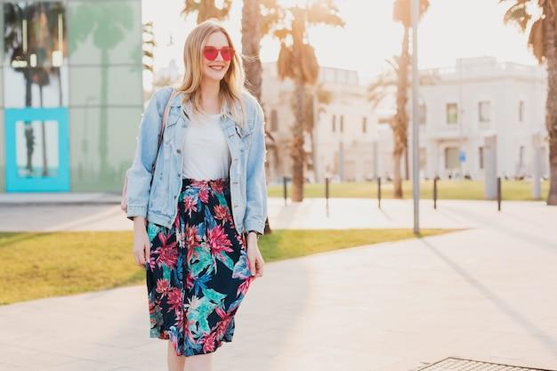 Улыбающаяся женщина гуляет по городской улице в стильной юбке с принтом и джинсовой куртке oversize в розовых очках