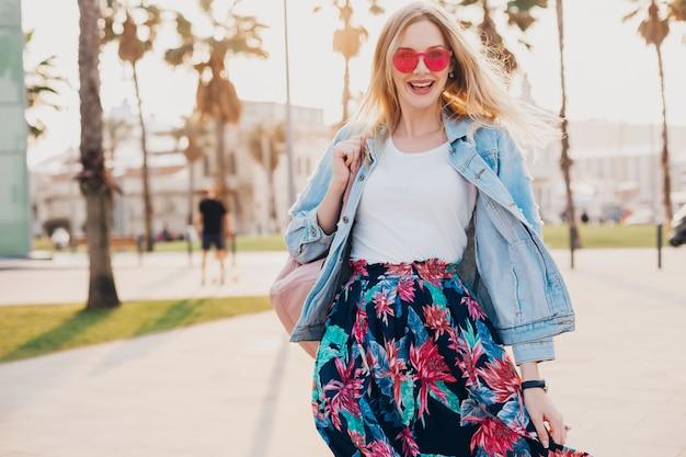 ピンクのサングラスを身に着けているスタイリッシュなプリントスカートとデニムの特大ジャケットで街を歩いて笑顔の女性