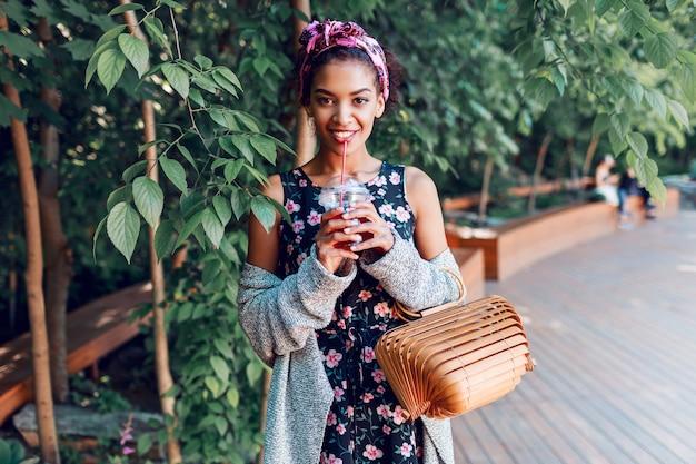 Улыбающаяся женщина гуляет в солнечном парке и пьет лимонад