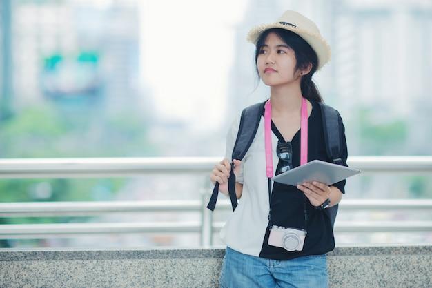 산책로 및 백그라운드에서 건물 도시 광경을 감상하는 젊은 아가씨 야외 산책, 웃는 여자.