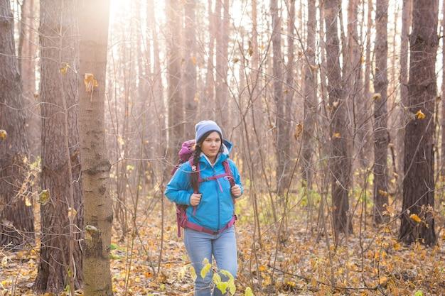 가 자연 배경 위에 배낭과 함께 걷는 웃는 여자.