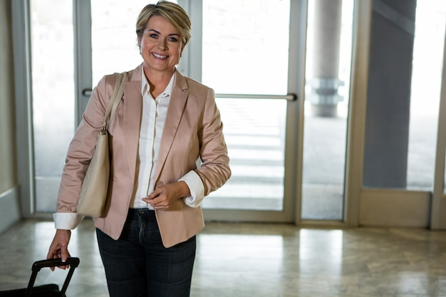 空港ターミナルでトロリーバッグで歩く笑顔の女性
