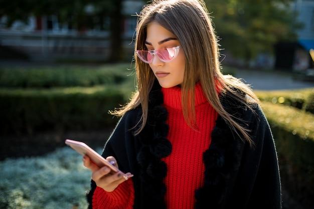 Una donna sorridente cammina lungo la strada di central park city e usa il suo telefono