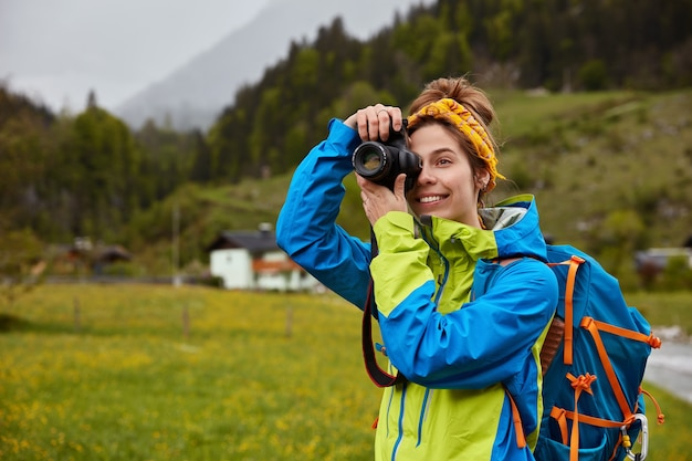 Smiling woman wanders in beautiful mountain countryside, keeps camera near eye, makes photo dressed in casual jacket