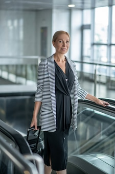 Smiling woman in ward and jacket on escalator