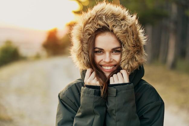 Улыбающаяся женщина теплые куртки с капюшоном крупным планом путешествия природа солнце. фото высокого качества