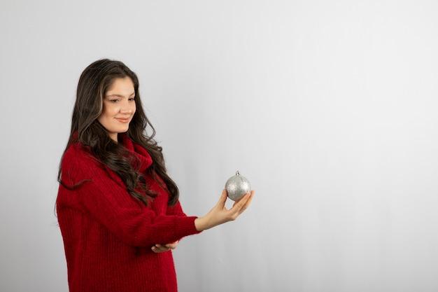 Donna sorridente in maglione rosso caldo che offre una palla di natale.
