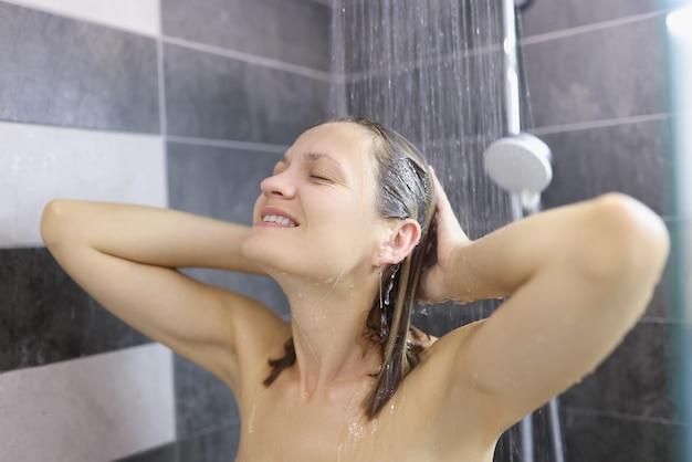 Улыбающаяся женщина, моющая волосы в душе в ванной комнате