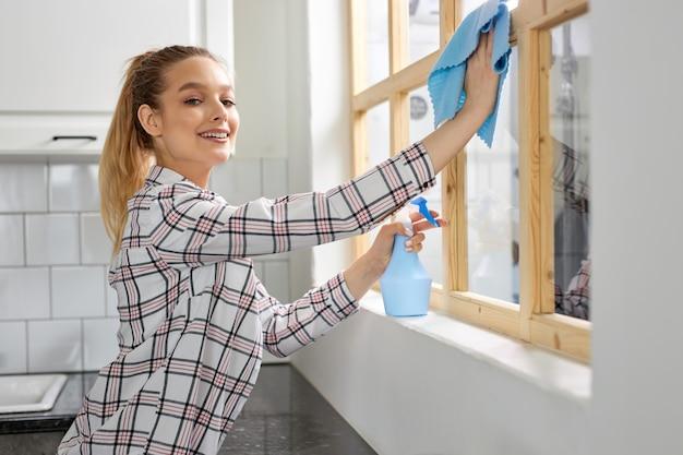 Smiling woman washing window with sponge rag cleaning window wiping dirt