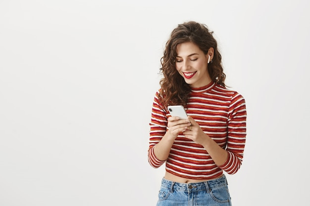 Smiling woman watching video on mobile phone in wireless earphones