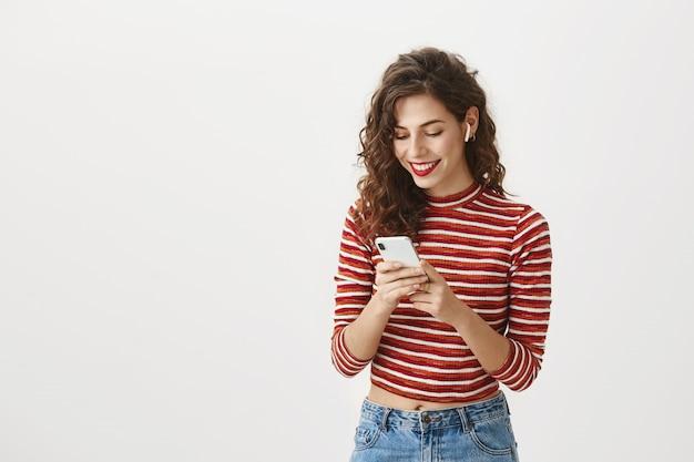 Улыбающаяся женщина смотрит видео на мобильном телефоне в беспроводных наушниках