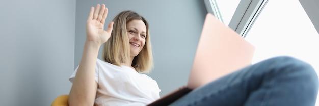 Улыбающаяся женщина машет рукой на ноутбук