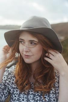 自然の中で帽子をかぶって笑顔の女性